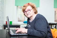 Senior age woman sitting at table with laptop, looking at camera Royalty Free Stock Photo