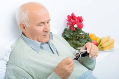 Senior aged man pours himself cough syrup. Cough syrup time. Gloomy aged man look down on the spoon while pouring himself cough syrup Royalty Free Stock Image