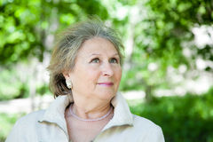 Senior aged woman outdoors in park looking up Royalty Free Stock Photography
