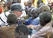 Senior aid relief volunteer smiling laughing with old African men Uganda, Africa