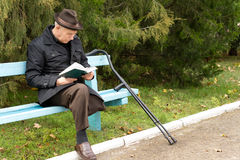 Senior amputee enjoying his book in the sunshine. Sitting on a park bench with his crutches alongside him in a hat and warm coat Stock Photography