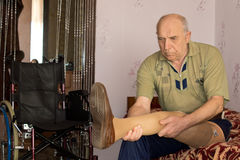 Senior amputee testing his prosthetic leg. As he sits on the bed near his wheelchair Royalty Free Stock Photo