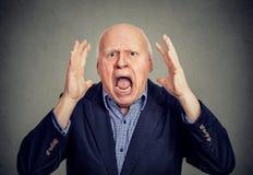 Senior angry man screaming. Arms raised up stock image