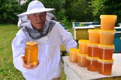 Senior apiarist presenting jar of fresh honey in apiary. In the springtime Stock Images