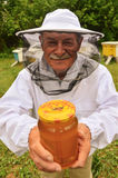 Senior apiarist presenting jar of fresh honey in apiary. In the springtime Stock Image
