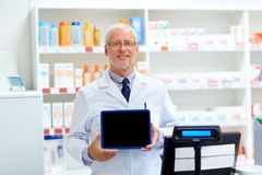 Senior apothecary at pharmacy cash register. Medicine, healthcare and people concept - senior apothecary at pharmacy cash register Stock Photography