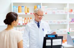 Senior apothecary reading prescription at pharmacy. Medicine, healthcare and people concept - senior apothecary reading prescription from customer at pharmacy royalty free stock photo
