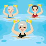 Senior Aqua Gym Dumbbells. Small group of senior women making aqua gym exercises with dumbbells in swimming pool at the sports center Royalty Free Stock Image