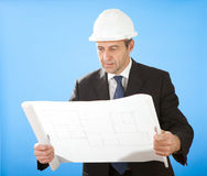 Senior architect holding blueprints on sky Stock Photos