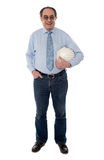 Senior architect holding hard-hat, full length. Senior architect holding helmet in one hand, full length view Royalty Free Stock Image