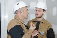 Senior architect and young builder discussing new project Stock Photography