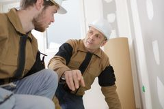 Senior architect and young builder discussing project Royalty Free Stock Photo