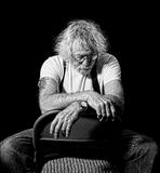 Sad old man. Senior with arms crossed on a chair with a look of dejection in monochrome isolated on black Stock Photos