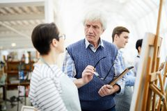 Senior Art Teacher Talking to Student. Portrait of mature art teacher frowning while helping student painting picture on easel in art class, copy space royalty free stock photo
