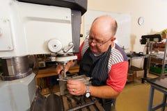 Senior artisan working. Senior male artisan working on industrial drilling machine in workshop Royalty Free Stock Photo