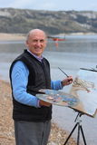 Senior artist painting by the sea. Stock Photo