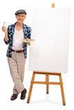 Senior artist standing by a blank canvas. Full length portrait of a senior artist standing next to a blank canvas isolated on white background stock photo