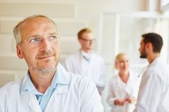 Senior as chief physician. At hospital with colleagues royalty free stock photo