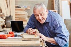 Senior as craftsman measuring wood. At carpentry shop Royalty Free Stock Photos