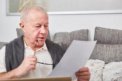 Senior as retiree holds document. For finance documentation Royalty Free Stock Images