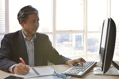Senior asain business man writing and working on pc computor Stock Image