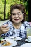 Senior asia woman. Eating food royalty free stock photography