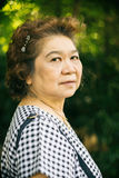 Senior asia woman. Portrait of senior asia woman in the park Royalty Free Stock Images