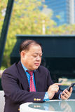 Senior Asian businessman in suit using smart phone Royalty Free Stock Photo