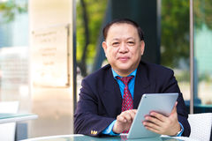 Senior Asian businessman in suit using tablet PC Stock Images