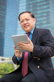 Senior Asian businessman in suit using tablet PC Stock Photo