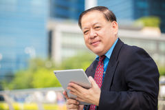 Senior Asian businessman in suit using tablet PC Stock Photos