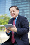 Senior Asian businessman using tablet PC Stock Images