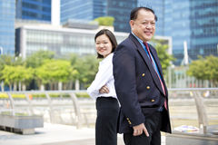 Senior Asian businessman and young female Asian executive smiling portrait. Outdoor Royalty Free Stock Image