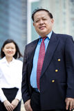 Senior Asian businessman and young female Asian executive smiling portrait. Outdoor Royalty Free Stock Images