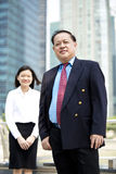 Senior Asian businessman and young female Asian executive smiling portrait. Outdoor Royalty Free Stock Photography