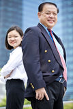 Senior Asian businessman and young female Asian executive smiling portrait. Outdoor Stock Photo