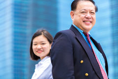 Senior Asian businessman and young female Asian executive smiling portrait. Outdoor Stock Images
