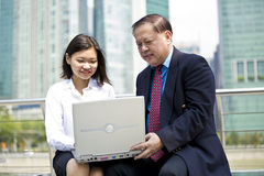 Senior Asian businessman and young female Asian executive using laptop PC Stock Image