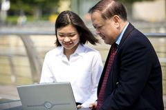 Senior Asian businessman and young female Asian executive using laptop PC Stock Photography