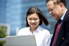 Senior Asian businessman and young female Asian executive using laptop PC Royalty Free Stock Photos