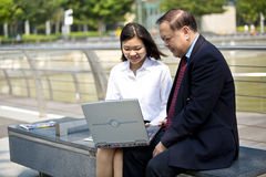 Senior Asian businessman and young female Asian executive using laptop PC Royalty Free Stock Photography