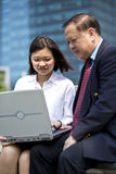 Senior Asian businessman and young female Asian executive using laptop PC Stock Images