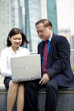 Senior Asian businessman and young female Asian executive using laptop PC Stock Photo