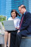 Senior Asian businessman and young female Asian executive using laptop PC Royalty Free Stock Images
