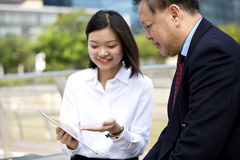 Senior Asian businessman and young female Asian executive using tablet PC Stock Photos