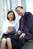 Senior Asian businessman and young female Asian executive using tablet PC Stock Photo