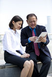 Senior Asian businessman and young female Asian executive using tablet PC Royalty Free Stock Photography