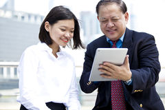 Senior Asian businessman and young female Asian executive using tablet PC Royalty Free Stock Image