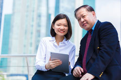 Senior Asian businessman and young female Asian executive using tablet PC Stock Images