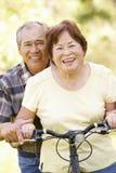 Senior Asian couple both sitting on one bike in park Stock Photo